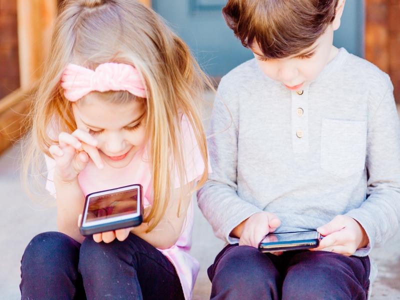 Dečak i devočica koriste mobilni telefon